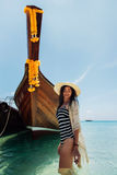 Beautiful young girl model in a swimsuit posing against a traditional Thai wooden boat Stock Photos