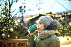 Beautiful young girl with a mug of hot drink at the Christmas market in Moscow. stock images