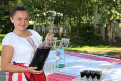 Beautiful young girl in the national Ukrainian costume presents national alcoholic drink. At the presentation of the menu of Ukrainian national cuisine in the stock photos