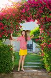 Beautiful young girl near the arch with red flowers Royalty Free Stock Photos