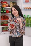 Beautiful young girl near the Fridge with healthy food. Stock Images