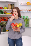 Beautiful young girl near the Fridge with healthy food. Stock Photo