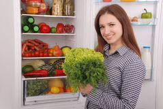 Beautiful young girl near the Fridge with healthy food. Royalty Free Stock Images