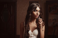 Beautiful young girl in negligee lipstick, looking in the mirror Stock Images