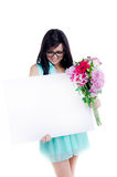 Beautiful young girl. Beautiful young nerd girl with flowers in summer dress holding a white sign/hiding behind a white sign Stock Photos