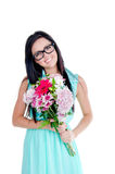 Beautiful young girl. Beautiful young nerd girl in studio standing with flowers and smiling looking surprised Royalty Free Stock Images