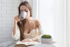 Beautiful young girl in a nightgown sits in the morning at the glass table, looks out the window and drinks coffee royalty free stock images