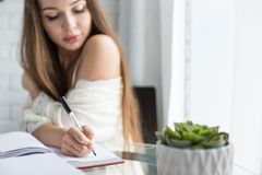 A beautiful young girl in a nightgown is sitting in the morning at a glass table and writes her thoughts in a notebook. royalty free stock images
