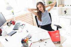 Beautiful young girl in the office sits at the table, laying her hands behind her head. A charming young girl in a black skirt and blue blouse is working in a Royalty Free Stock Photography