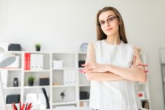 Beautiful young girl in an office is standing near a table. Charming young girl with glasses and a white blouse in a bright office. photo with depth of field Royalty Free Stock Image