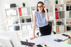 Beautiful Young girl in the office is standing near the table and fixes her glasses with her hand. A charming young girl in a black skirt and blue blouse is Stock Photography