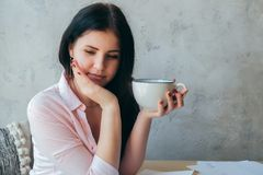 A beautiful young girl office worker holds in her hands and drinks coffee in a large cup. A teenage student student is drinking. Tea thinking about something stock image