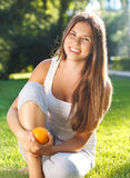 Beautiful young girl with open smile holding orange Royalty Free Stock Photos
