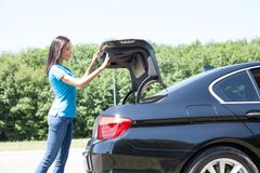 Beautiful young girl is opening a boot of the car Royalty Free Stock Photography