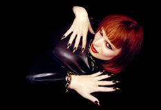 Beautiful young girl. A beautiful young girl with orange hair,makeup and with sharp fingernails on a dark background royalty free stock photography