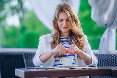 Beautiful young girl in outdoor cafe reading a Stock Photography