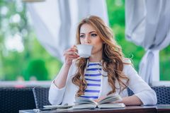 Beautiful young girl in outdoor cafe reading a Royalty Free Stock Photos