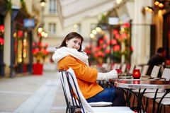 Beautiful young girl in an outdoor Parisian cafe Stock Images