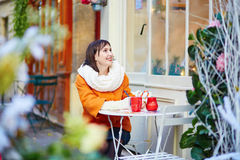 Beautiful young girl in an outdoor Parisian cafe Stock Image