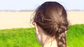 Beautiful young girl outdoors looking, hair blowing in wind on nature background. stock video