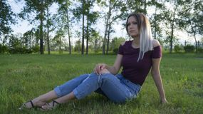814fdbefd1aa Beautiful young girl outdoors sitting on green grass. In the background  trees royalty free stock