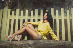 Beautiful young girl outdoors. Sitting by the wooden fence. Spring mood. Young woman outdoors royalty free stock photos