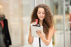 Beautiful young girl paying by credit card for Stock Photography