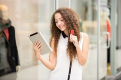 Beautiful young girl paying by credit card for Royalty Free Stock Image