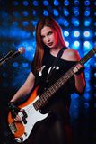Beautiful young girl performs songs on stage in rock style Stock Image