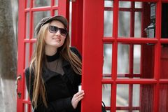 Beautiful young girl in a phone booth. The girl is talking on th Royalty Free Stock Photo