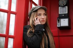 Beautiful young girl in a phone booth. The girl is talking on th Stock Photo