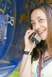 Beautiful young girl in a phone booth. The girl is talking on the phone from the payphone. pretty teen girl talking by public. Telephone stock image