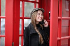Beautiful young girl in a phone booth. The girl is talking on th. E phone from the payphone. English telephone booth in the street and a woman talking on the Royalty Free Stock Images