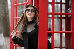 Beautiful young girl in a phone booth. The girl is talking on th Stock Photos