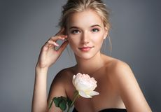 Photo of blonde girl with rose. Beautiful young girl. Photo of blonde girl with rose on grey background. Skin care concept stock photos