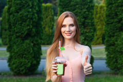 Beautiful young girl in a pink dress drinking juice in the garden Royalty Free Stock Images
