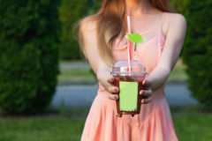 Beautiful young girl in a pink dress drinking juice in the garden Royalty Free Stock Photo