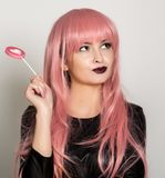 Beautiful young girl with pink hair, smile and brigth light with candy lolipop.  Royalty Free Stock Photo