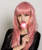 Beautiful young girl with pink hair, smile and brigth light with candy lolipop.  Royalty Free Stock Image