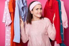 Beautiful young girl in pink shirt has shopping in fashion boutique. Pretty lady chooses dress in clothes store. Woman finds. Modern dress while curving her royalty free stock image