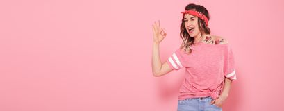 Beautiful young girl in pink t-shirt with decal water tattoo flowers sticker. And smiling on pink background. Shows hand OK. Place for text. Advertising concept stock image