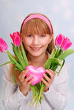 Beautiful young girl with pink tulips and heart Royalty Free Stock Photography