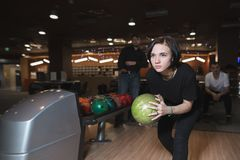 Beautiful young girl playing bowling. Woman with ball for bowling in hands in motion royalty free stock photos