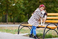Beautiful young girl playing with dog outdoors. Pet concept. Cute girl kid with doggie hugging in the park on the street bench. Having fun together outdoors on Stock Image