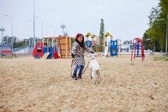 Beautiful young girl playing with dog outdoors. Pet concept. Cute girl kid with doggie playing in the playground. Having fun together outdoors on the nature Stock Photos