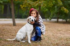 Beautiful young girl playing with dog outdoors. Pet concept. Cute girl kid with doggie walking and hugging in the park. Having fun together outdoors on the Royalty Free Stock Images