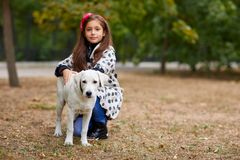 Beautiful young girl playing with dog outdoors. Pet concept. Cute girl kid with doggie walking in the park. Having fun together outdoors on the nature Stock Images