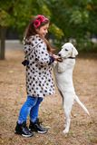 Beautiful young girl playing with dog outdoors. Pet concept. Cute girl kid with doggie walking in the park. Having fun together outdoors on the nature Royalty Free Stock Images
