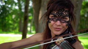 Beautiful young girl playing on electric violin on beautiful park. Sunny, windy day. The violinist smiles. Looks and smiles straight at the camera stock video