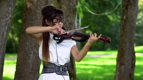 Beautiful young girl playing on electric violin on beautiful park. Sunny, windy day. The violinist smiles. Sun glare. Dancing and smiling stock video